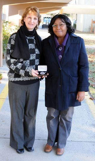 NWCC's Beverly Moore-Garcia, left, presents the Lieutenant Governor's Silver Medal to graduate Marjorie Ramdatt.